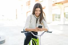 Businesswoman Searching Way In Navigation Via Cell Phone. Smiling and charming Latin woman on bicycle searching information via mobile phone in city stock photography