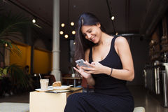 Smiling charming latin woman read good news on her mobile phone during breakfast in caffe terrace in summer day, Royalty Free Stock Photos