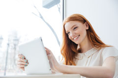 Smiling charming redhead young woman with tablet in cafe Royalty Free Stock Photography
