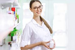 A smiling charming slim dark-haired lady with glasses, wearing a white coat, stands next to the shelf and shows a small royalty free stock photos