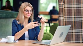 Smiling charming stylish businesswoman looking at screen of smartphone having positive emotion. Medium shot. Beautiful young business female enjoying break stock video footage