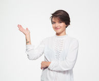 Smiling charming young female holding copyspace on palm Stock Image