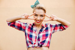 Smiling charming young pin-up woman showing peace sign. Over pink background Royalty Free Stock Photography