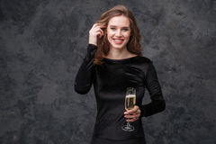 Smiling charming young woman holding glass of champagne Stock Photo