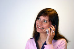 Smiling and chatting. Young cute woman talking and laughing with someone on the phone Stock Photo