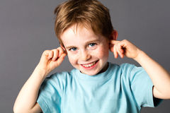 Smiling cheeky young boy ignoring his parent scolding with attitude Royalty Free Stock Photo