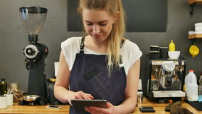 Smiling and cheerful barista using digital tablet for work stock video footage