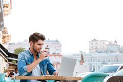 Smiling cheerful casual man using laptop outdoors and drinking coffee Stock Photo