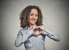 Smiling cheerful happy young woman making heart sign with hands Stock Photography