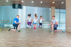 Smiling cheerful kids in school age playing together with jumping rope in gym. Children at physical education lesson in. School gym Royalty Free Stock Image