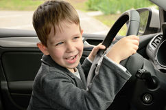 Smiling cheerful little boy driving Stock Photo