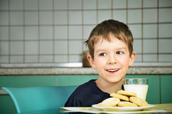 Smiling cheerful little boy sitting at the dinner table.  horizo Stock Image