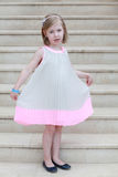 Smiling cheerful little girl in a beautiful beige and pink gown Royalty Free Stock Photography