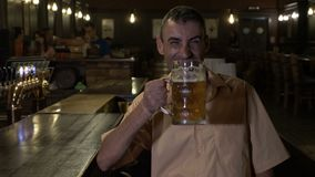 Smiling cheerful man drinks beer at the bar and cheers looking at camera -. Smiling cheerful man drinks beer at the bar and cheers looking at camera stock video footage