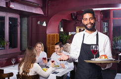 Smiling cheerful waiter taking care of adults Royalty Free Stock Photos