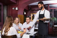 Smiling cheerful waiter taking care of adults Royalty Free Stock Images