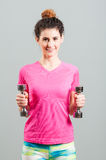 Smiling cheerful woman exercising and training with dumbbells Stock Photography
