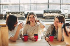 Smiling cheerful woman talk to her friends. Smiling cheerful women talk to her friends. Group of people enjoying coffee and conversation at cafe. People, leisure royalty free stock photos