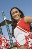 Smiling Cheerleader holding trophy Stock Photo