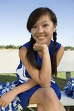 Smiling Cheerleader sitting on bench royalty free stock photos