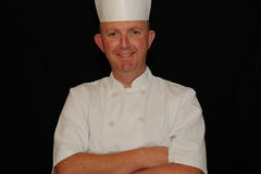 Smiling chef. Portrait of a smiling, proud chef on black studio background with space for text Royalty Free Stock Photos