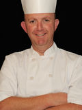Smiling Chef. A portrait of a smiling middle-aged chef on a black background Royalty Free Stock Images