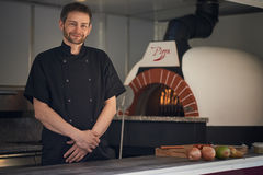 Smiling chef baking pizza. Smiling chef baking or flame grilling an Italian pizza in a modern wood oven at a pizzeria Stock Images
