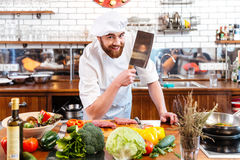 Smiling chef cook with cleaver knife cutting meat and vegetables. Smiling attractive chef cook with cleaver knife cutting meat and vegetables on the kitchen royalty free stock photos
