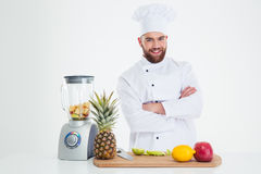 Smiling chef cook standing with arms folded. Portrait of a smiling chef cook standing with arms folded near table with fruits isolated on a white background royalty free stock images