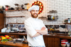Smiling chef cook standing with hands folded on the kitchen. Smiling attractive chef cook with beard standing with hands folded on the kitchen stock photo