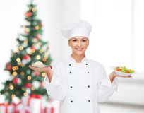 Smiling chef with cupcake and salad on plates Royalty Free Stock Images