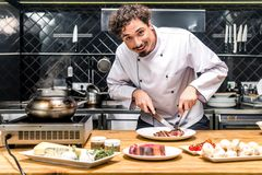smiling chef cutting fried meat with knife royalty free stock photography