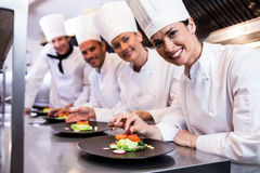 Smiling chef while decorating food plate Stock Photography