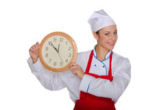 Smiling chef demonstrates clock Royalty Free Stock Photography
