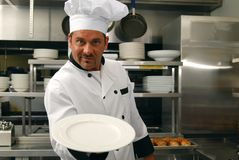 Smiling chef with empty plate Stock Photo