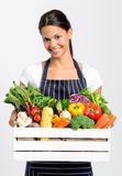 Smiling chef with fresh local organic produce. Portrait of happy indian woman chef holding a crate full of fresh organic vegetables on grey background, promoting Stock Image
