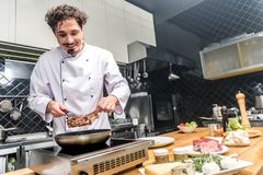 smiling chef frying meat stock photography