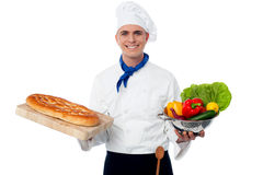 Smiling chef holding bread and vegatables Royalty Free Stock Photo