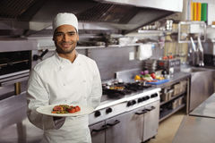 Smiling chef holding delicious dish in kitchen Royalty Free Stock Photo