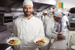 Smiling chef holding delicious dish in kitchen Royalty Free Stock Photography