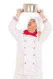 Smiling chef holding saucepan over head  weraing red and white u Royalty Free Stock Images