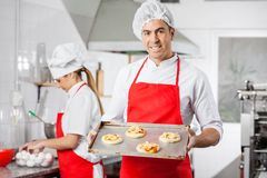 Smiling Chef Holding Small Pizzas On Baking Sheet Royalty Free Stock Image