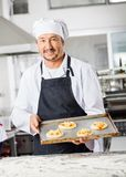 Smiling Chef Holding Small Pizzas On Baking Sheet Stock Image