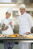 Smiling chef holding whisk while being watched by head chef Stock Images