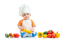 Smiling chef kid boy with vegetables isolated on white background Royalty Free Stock Images