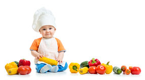 Smiling chef kid boy with vegetables isolated on white background Stock Image