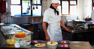 Smiling chef leaning on dessert counter stock video