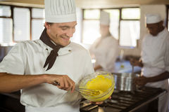 Smiling chef mixing dough Royalty Free Stock Image