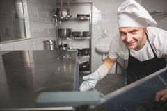 Smiling chef opening oven Royalty Free Stock Photo