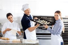 Smiling Chef Passing Baking Sheet To Colleague In Royalty Free Stock Photography